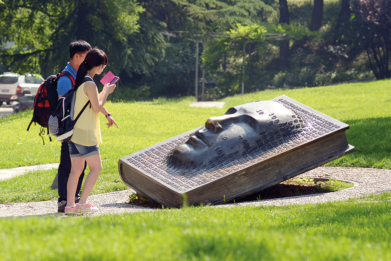 Visitors look at a bronze sculpture at Tsinghua University in Beijing, China
